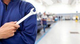 operaio con tuta da lavoro blu tiene in mano una chiave inglese in una officina