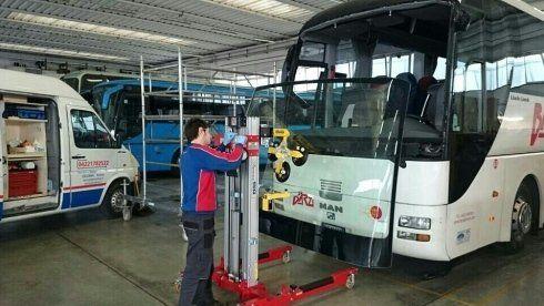 Un meccanico solleva un autobus con l'apposito cric elevatore