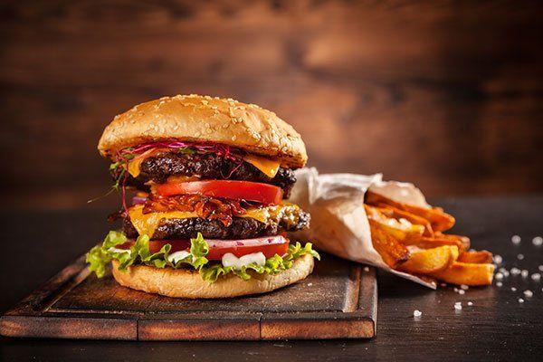 Super duplice hamburger con pomodoro,lattuga,bacon,carota,formaggio e patate fritte