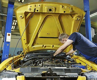 Technician looking under the hood of a yellow vehicle