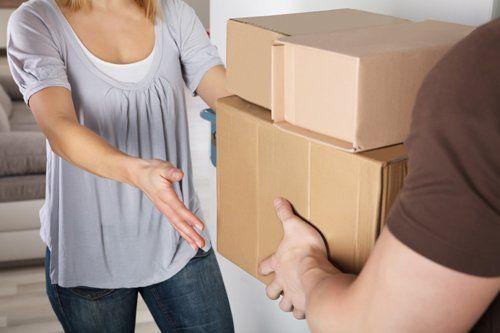 giovane donna che accetta una consegna delle scatole di cartone dal fattorino