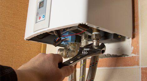 A plumber repairing pipework under a boiler