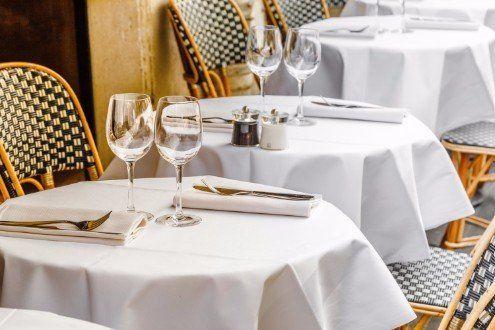 tavolini da bar con tovaglie bianche, bicchieri, posate e sedie