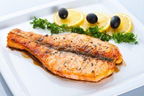piatto di pesce con insalata, limone ed olive nere