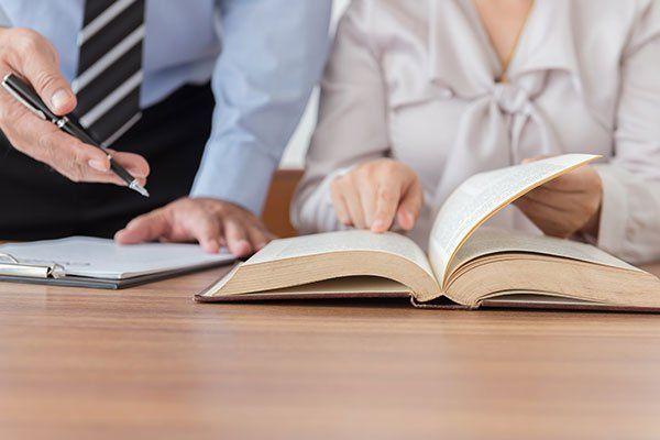 una donna seduta alla scrivania che indica un libro aperto e accanto un  uomo che indica lo stesso libro con una penna