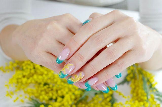 primo piano di unghie con smalto trasparente e verde smeraldo e disegno di mimosa