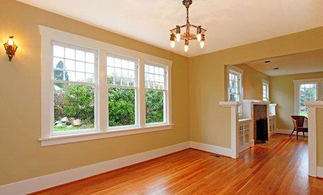 stanza luminosa con parquet tre finestre aperte e muro giallo ocra