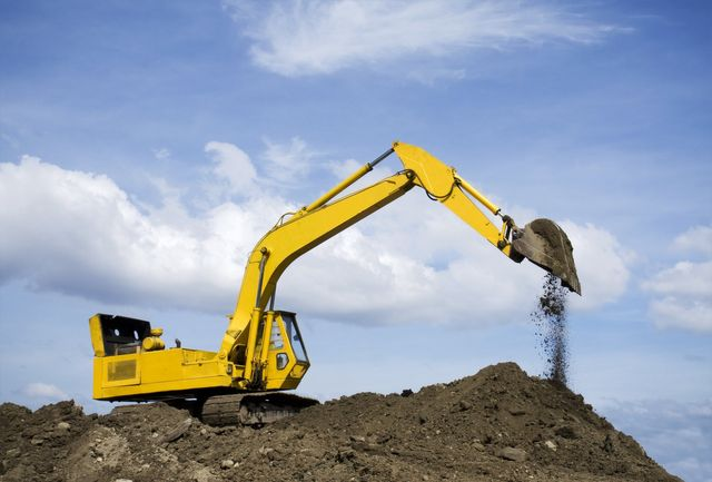 Earth moving machine clearing the soil