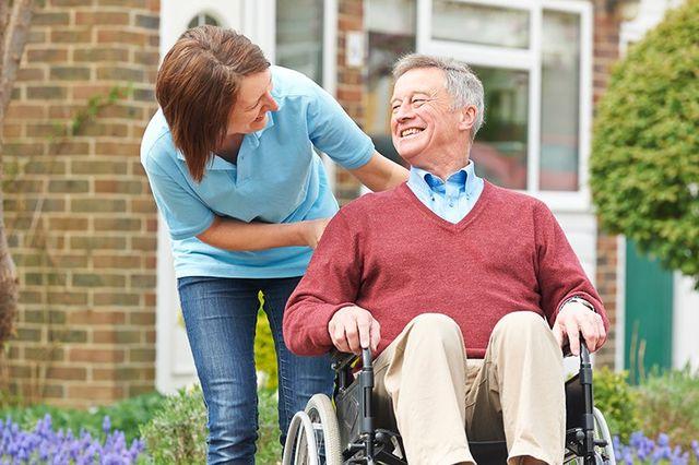 Carer Con Senior Man in sedia a rotelle