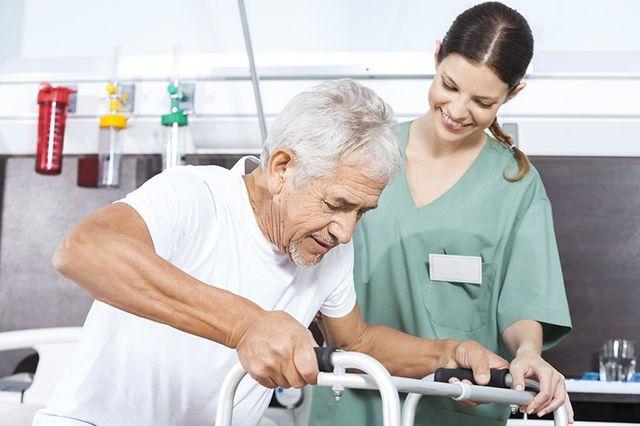Paziente maggiore che è assistita da Infermiera In Utilizzando Walker