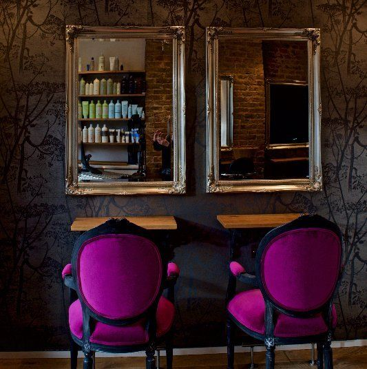 two wall mirrors and two styling chairs in black and purple