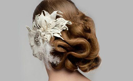 elaborate updo with feathers and flower in white