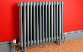 A grey radiator against a red wall