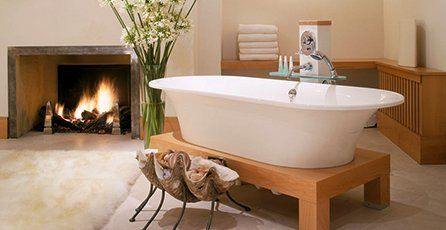 A curl-top bath on a wooden stand in front of a log fire