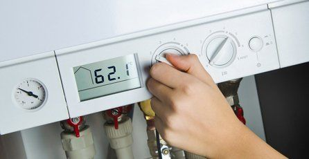 A hand programming the controls on a white boiler