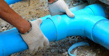 Gloved hands holding an aqua blue drain pipe