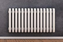 A white radiator on a grey wall