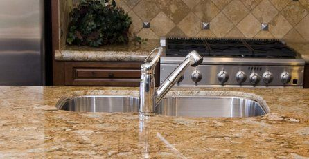 A chrome washbasin in a marble unit, opposite a chrome cooker