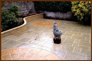 New patio in a garden with a water feature in the middle