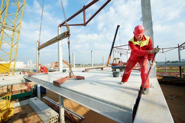 operaio lavora su tetto con impalcature