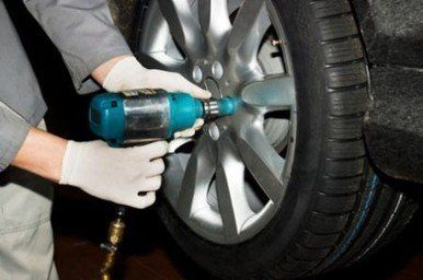 meccanico mentre cambia una ruota di una macchina in una officina