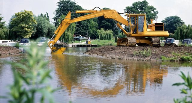 An earthmoving contractor clearing land by a lake in Wellington