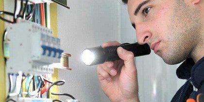 elettricista controlla fili elettrici con una luce