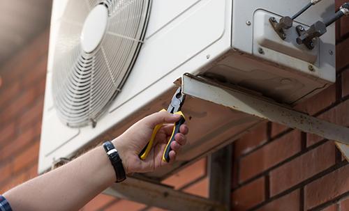 operaio mentre installa il motore del condizionatore
