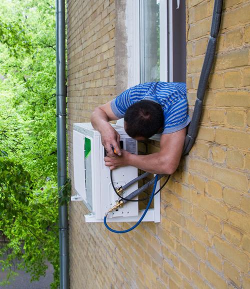 operaio ripara un condizionatoe esterno