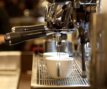due tazzine di espresso e una macchina del caffè