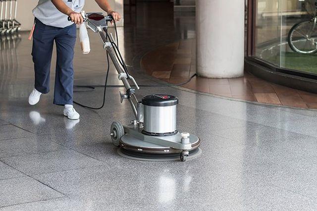 impiegato che pulisce il pavimento con una macchina