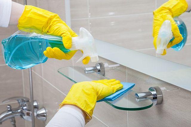 Mani che puliscono un bagno