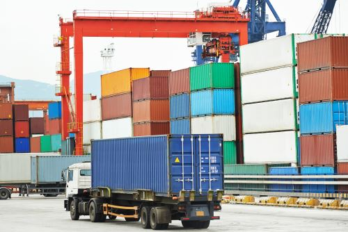 un camion in un deposito con dei container