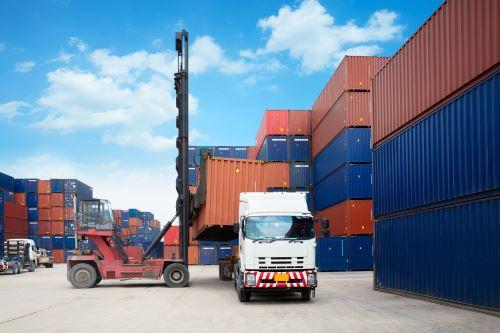 un camion e un muletto in una rimessa con dei container