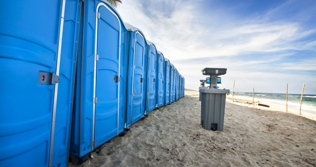 A long line of blue portable toilets on a beach