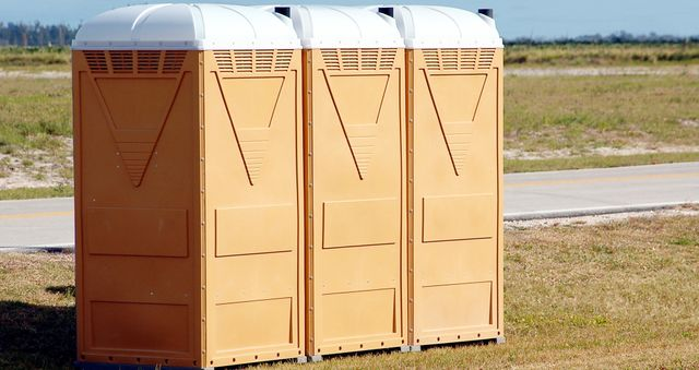 Three brown portable toilets