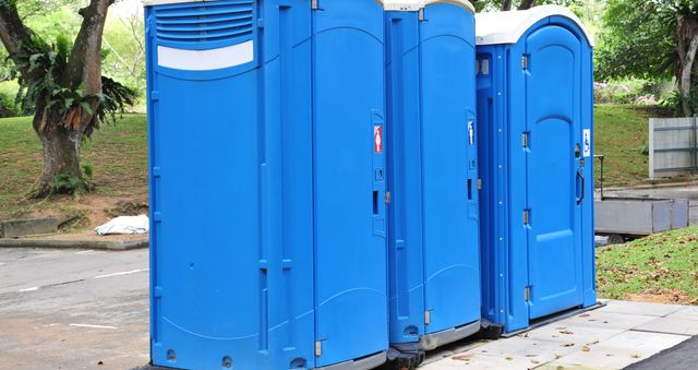 Three blue portable toilets