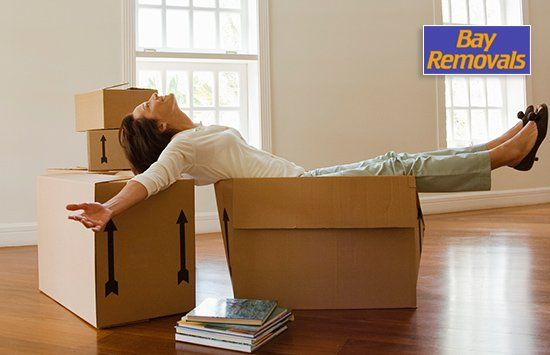 bay removals woman reclining on moving boxes