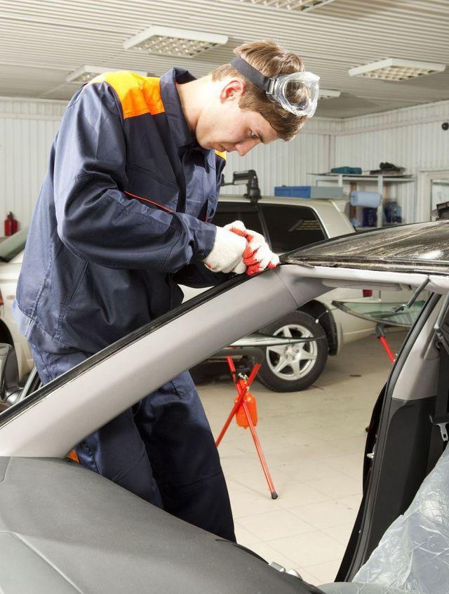 Car mechanic works on auto glass replacement in Waipahu, HI