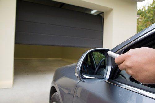 vista laterale di un auto da parcheggiare in un garage con la serranda a metà
