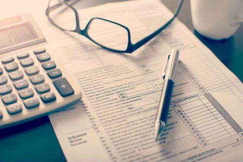 Modulo di ritorno di imposta sul reddito individuale, bicchieri, penna e calcolatrice sulla scrivania