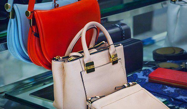 borse in pelle di color rosa, rosso e blu  esposte su piano in vetro