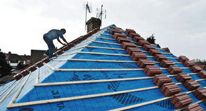 Roofer laying new tiles