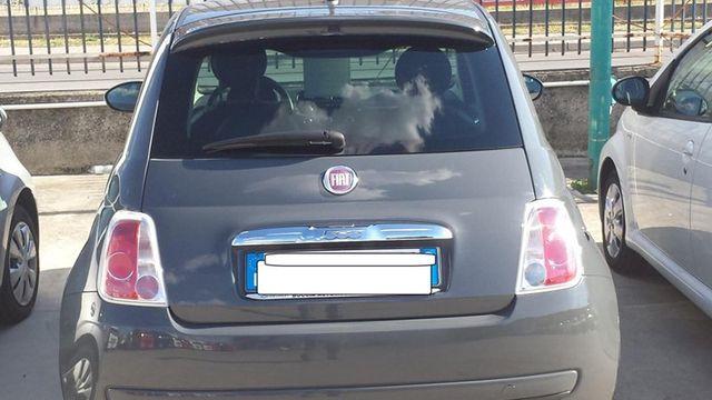 una Fiat 500 grigia scura vista da dietro
