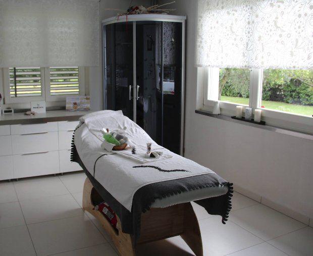un lettino, una cabina e un mobile con cassetti bianchi all'interno di un centro estetico