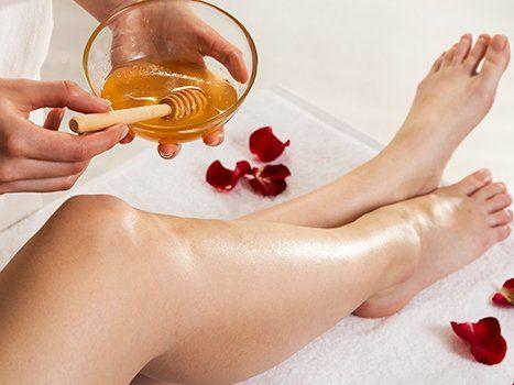 un'estetista con una bacinella di vetro in mano con dentro della cera e delle gambe di una donna e per terra dei petali rossi