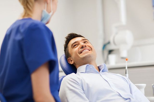 Female dentist with happy male patient