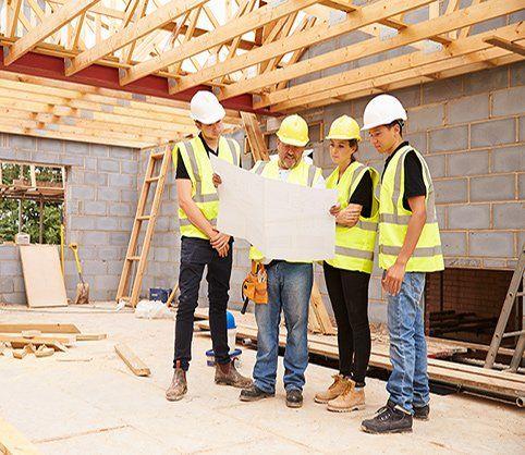 Operai discutendo il piano di costruzione nel cantiere a Cona