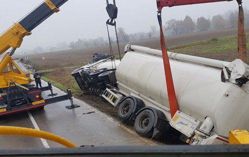 Un'autogru solleva un camion ribaltato fuori carreggiata