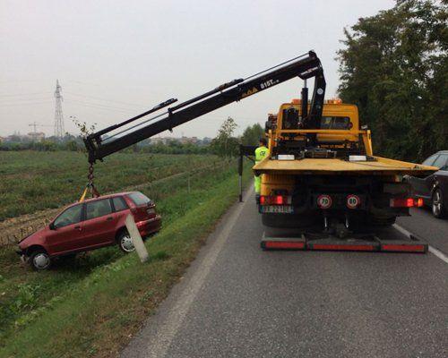 Un carro attrezzi solleva una macchina incidentata fuori carreggiata